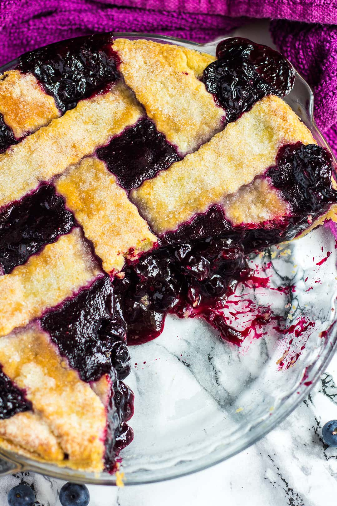 Overhead shot of homemade blueberry pie with slices removed in a glass pie dish.
