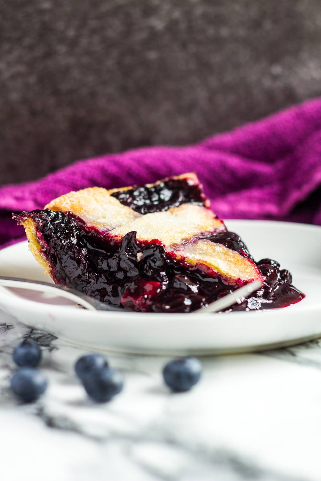 A slice of homemade blueberry pie served on a small white plate with a fork.
