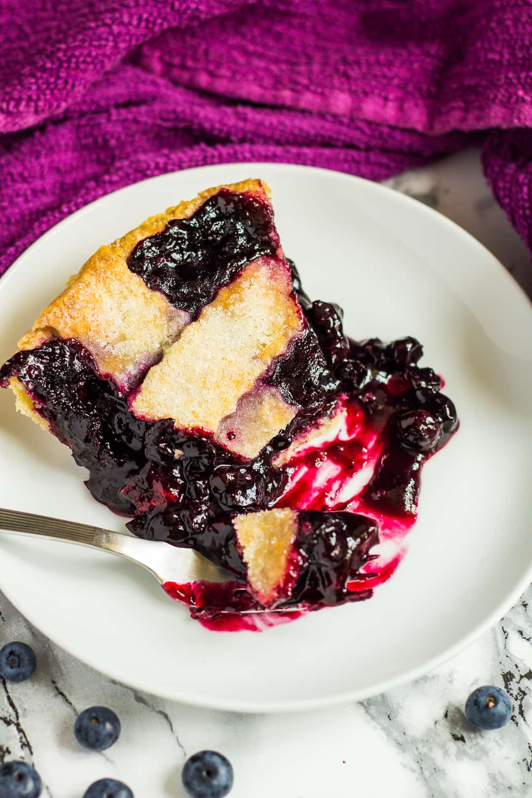 Overhead shot of a slice of homemade blueberry pie on a small white plate with a fork.