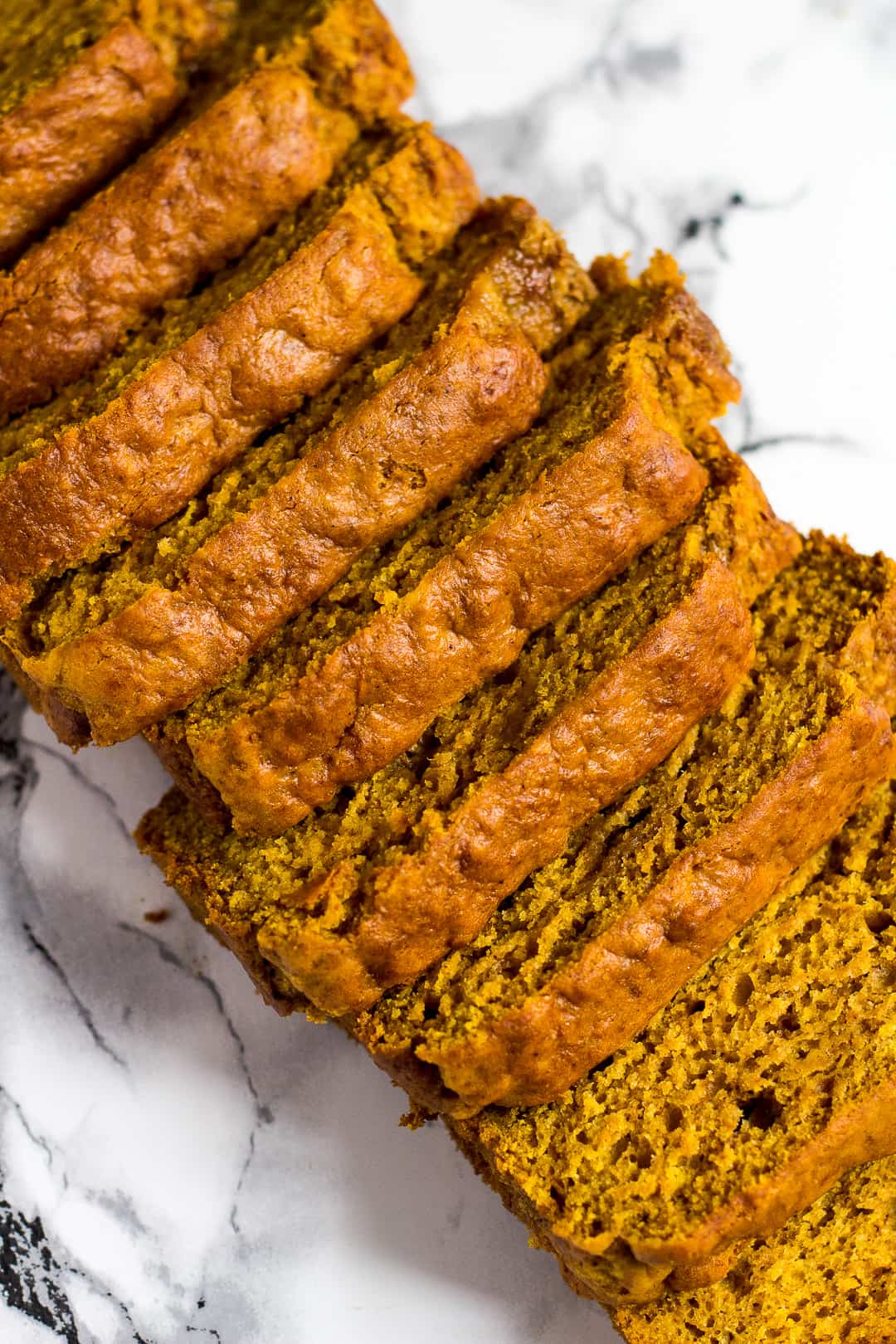 Overhead shot of pumpkin bread slices overlapping each other.