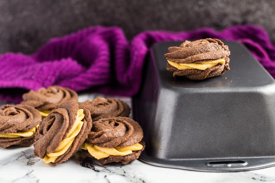 A pile of chocolate pumpkin Viennese whirls on top of and next to a loaf pan.