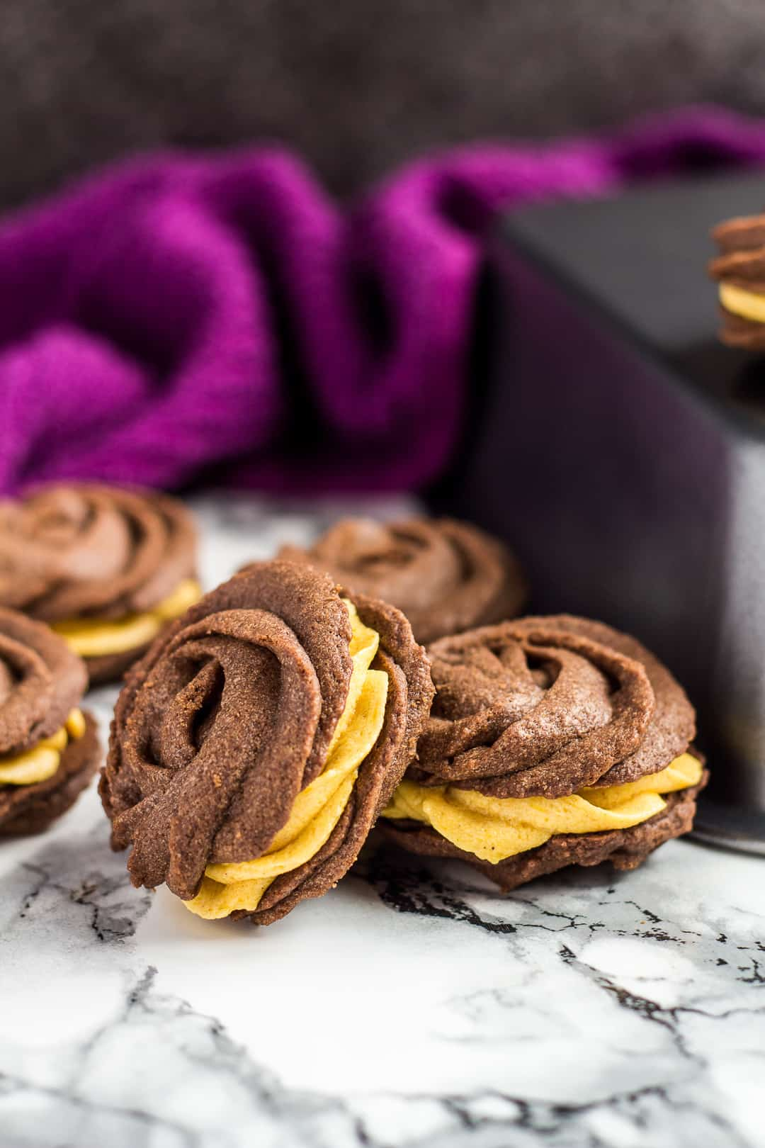 Chocolate pumpkin Viennese whirls scattered next to upside down loaf pan.