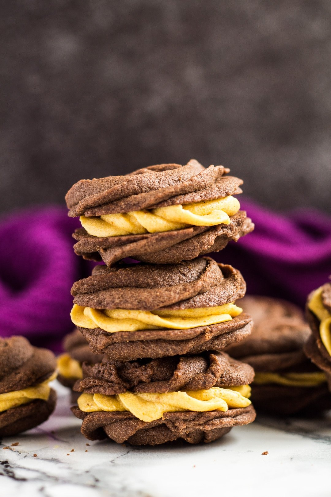 A stack of chocolate pumpkin Viennese whirls.