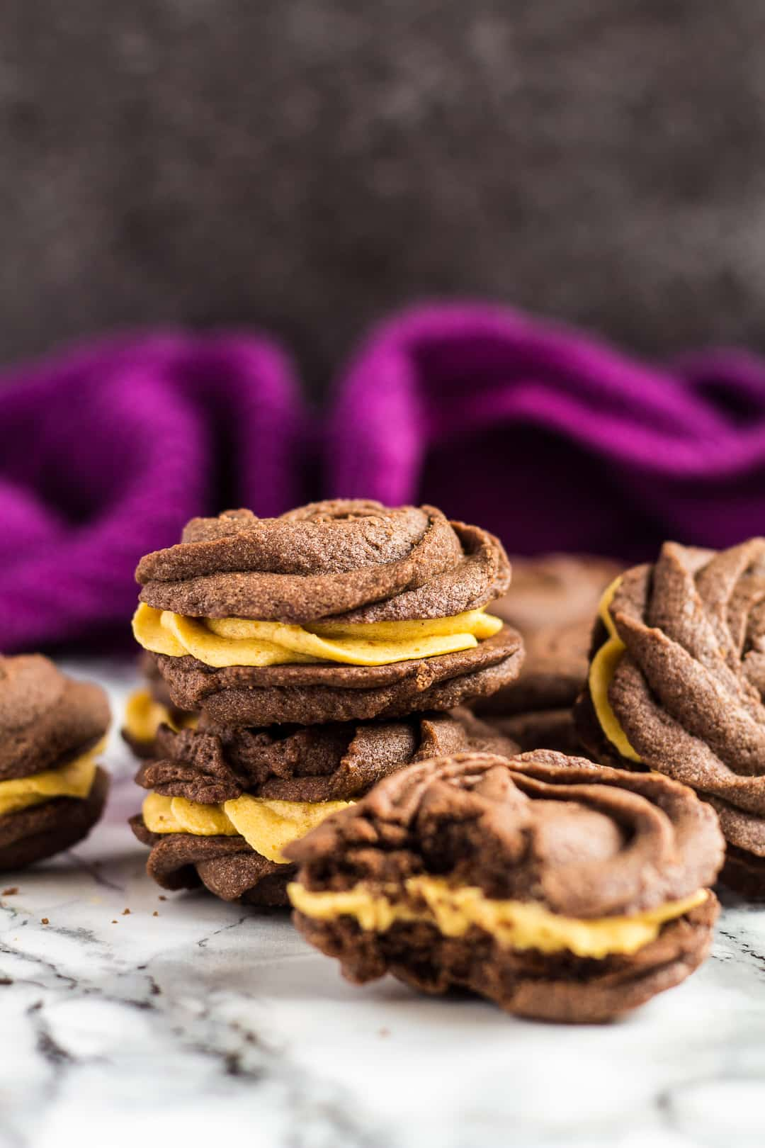 A chocolate pumpkin Viennese whirl on top of another one with more scattered around.