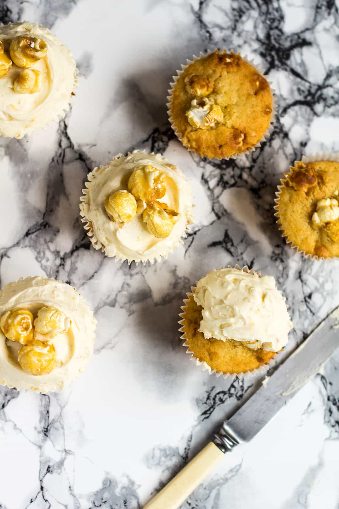 Overhead shot of toffee popcorn cupcakes being frosted.