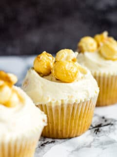 A row of three frosted toffee popcorn cupcakes.