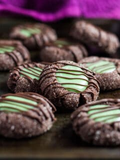 Chocolate thumbprint cookies with a mint filling on a baking tray.