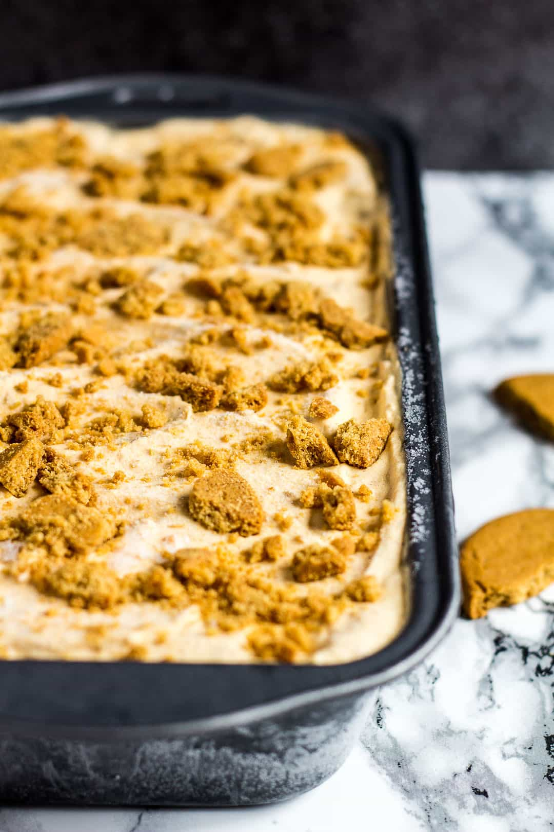 Pumpkin gingerbread ice cream in a loaf pan topped with broken ginger biscuits.