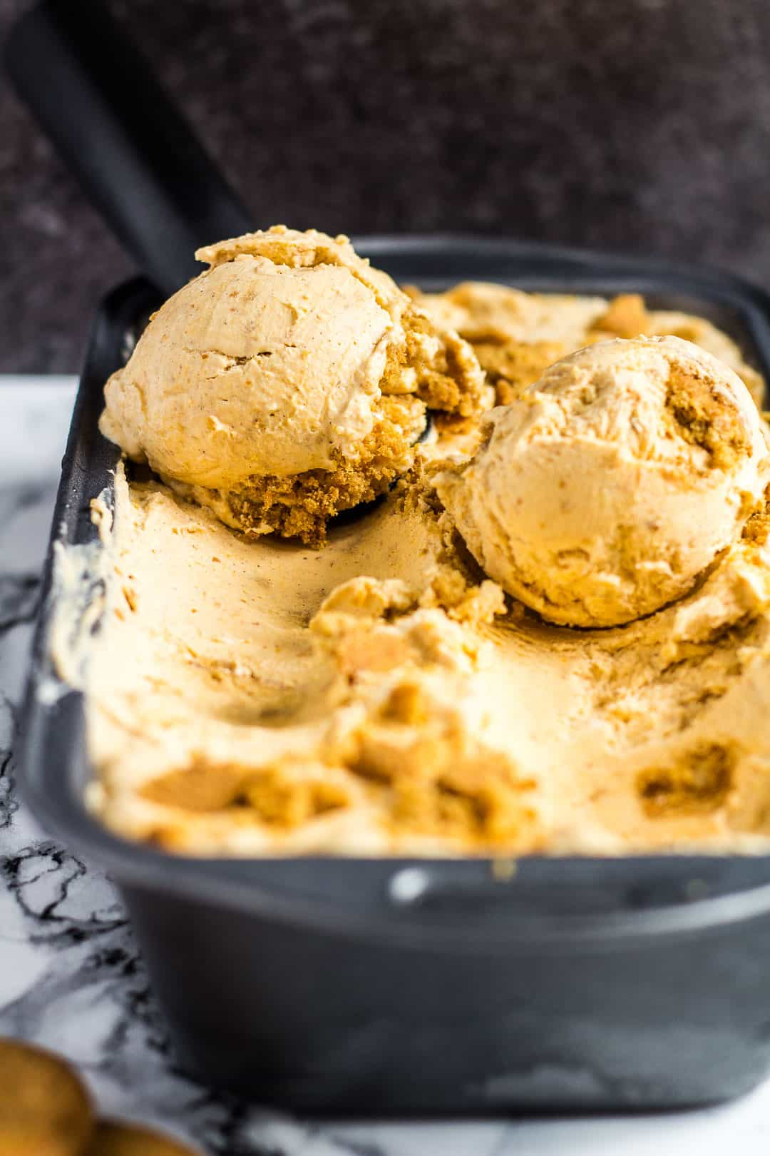 Pumpkin gingerbread ice cream in a loaf pan being scooped up.