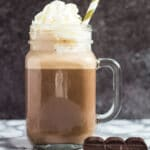 A mason jar filled with chocolate eggnog and whipped cream on top.