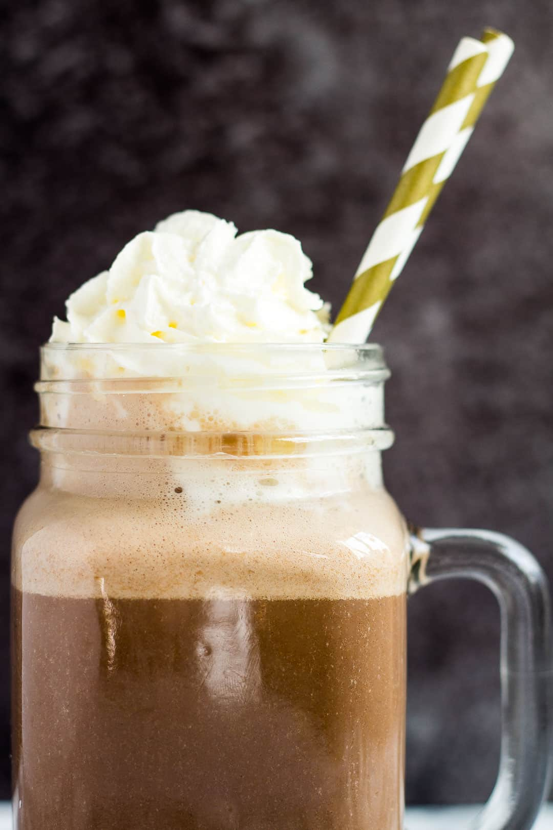 A close-up shot of a mason jar filled with chocolate eggnog with whipped cream on top.