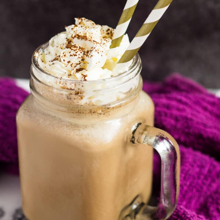 A mason jar filled with banana coffee milkshake with whipped cream and two straws.