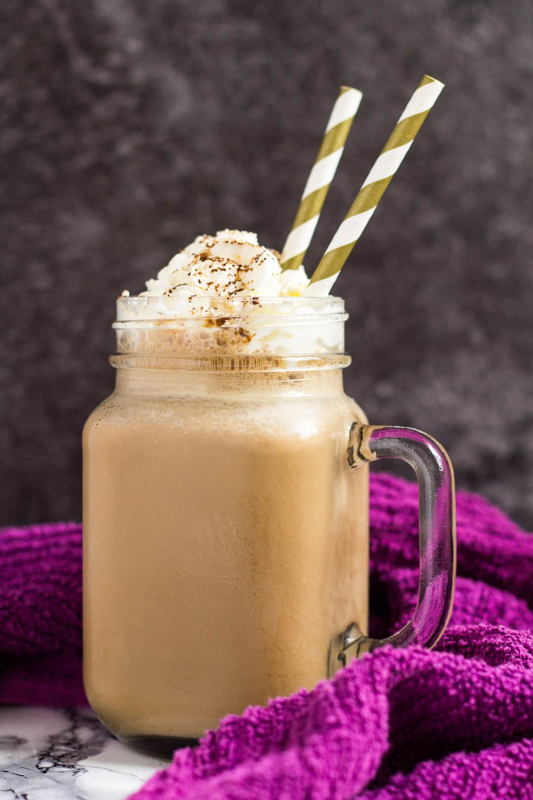 A mason jar filled with banana coffee milkshake with whipped cream on top.
