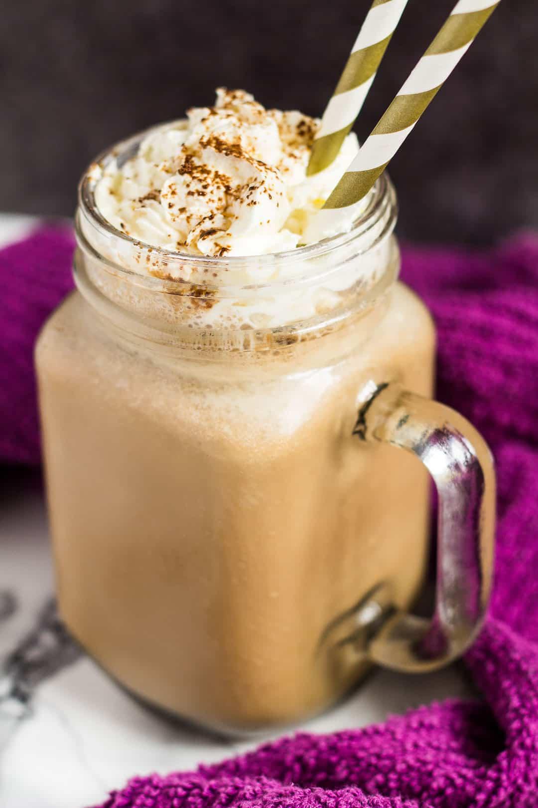 Banana coffee milkshake in a mason jar with whipped cream and two straws.