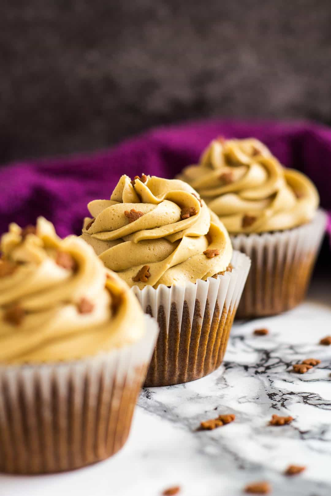 A row of three frosted gingerbread cupcakes.