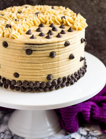 Mocha layer cake on a white cake stand.