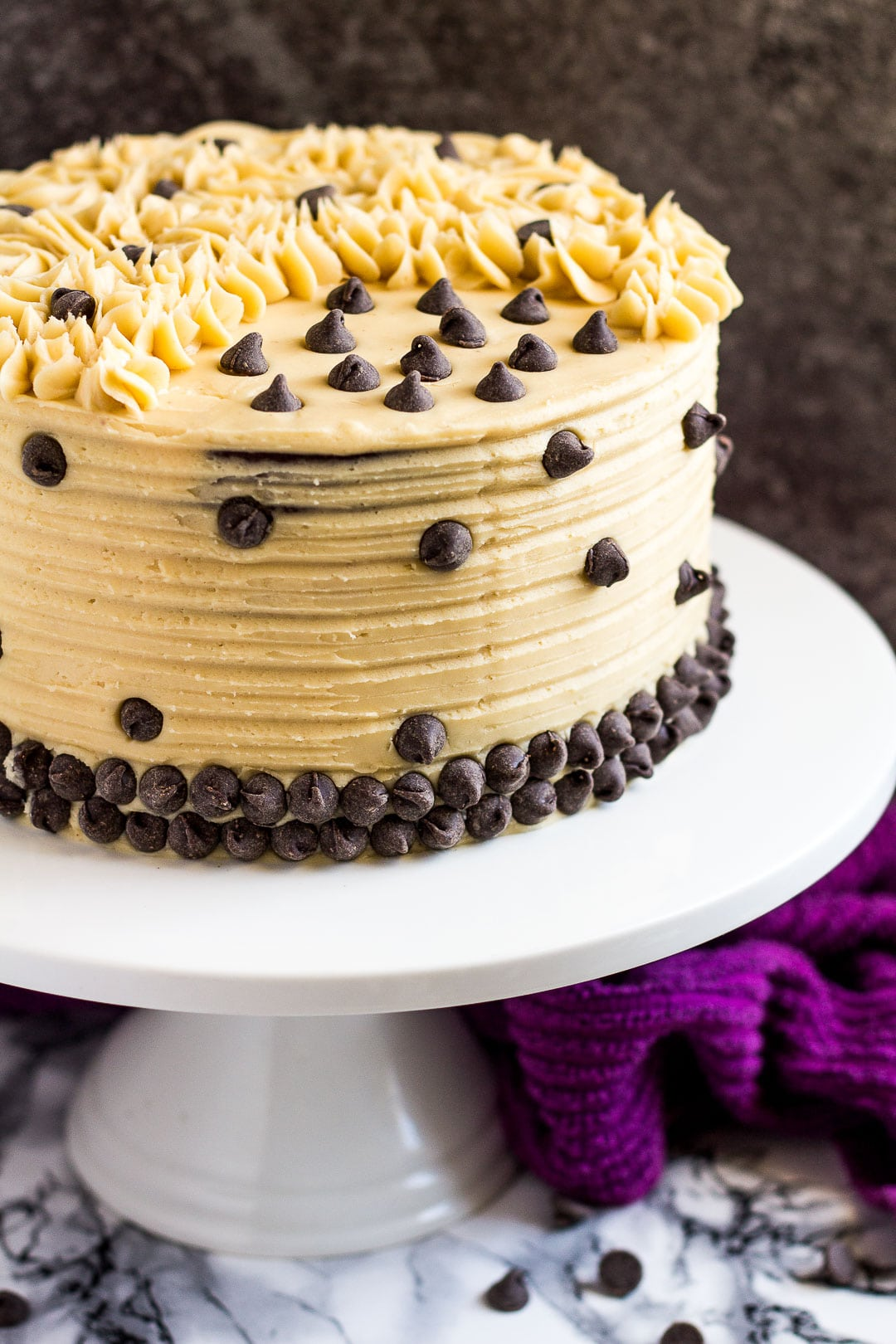 Mocha layer cake studded with chocolate chips on a white cake stand.