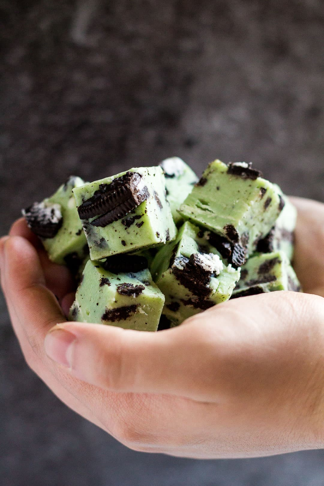 A pile of mint chocolate Oreo fudge pieces in cupped hands.