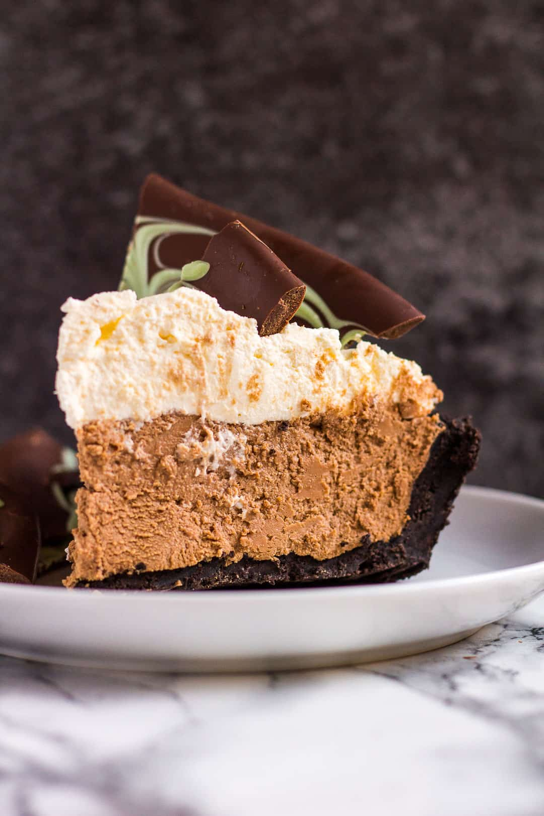Side-view shot of a slice of mint chocolate cream pie on a small white plate.