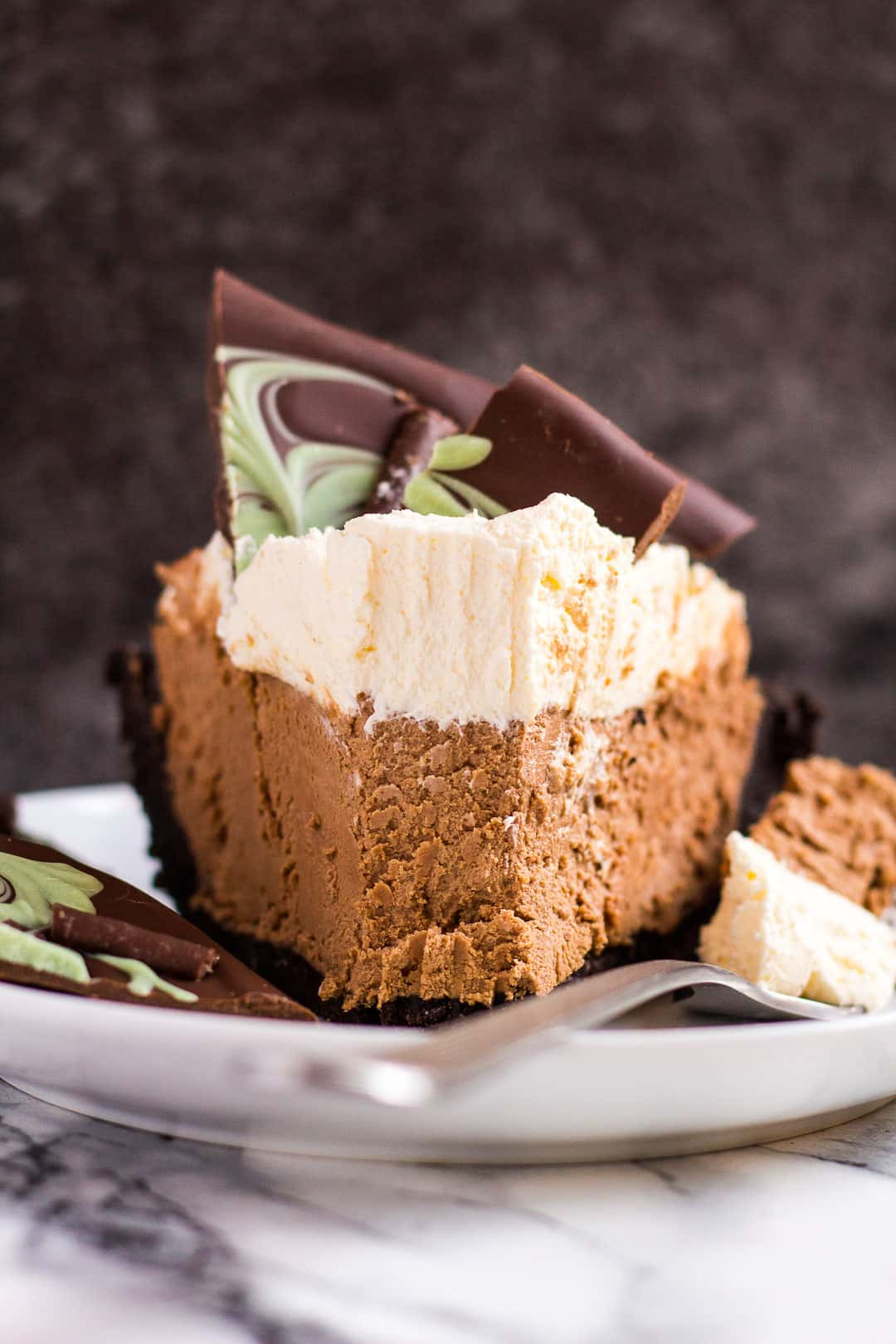 A slice of mint chocolate cream pie on a small white plate with a fork.