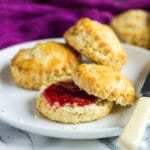 Classic English Scones served on a small white plate. One scone is cut in half and filled with strawberry jam.