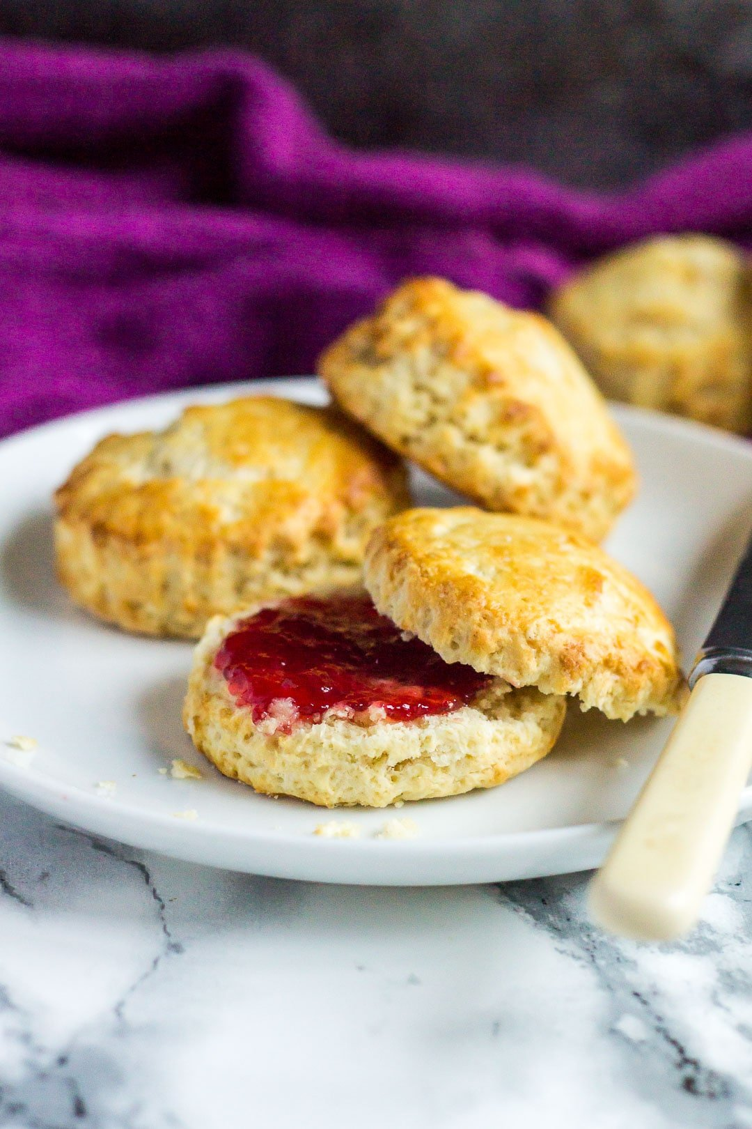 Classic English Scones with one cut in half served with strawberry jam on a small white plate with palette knife.