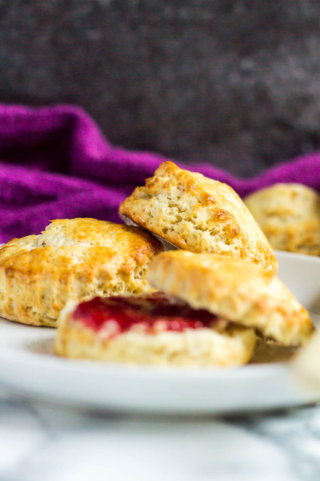 Classic English Scones served on a small white plate with one cut in half and spread with strawberry jam.
