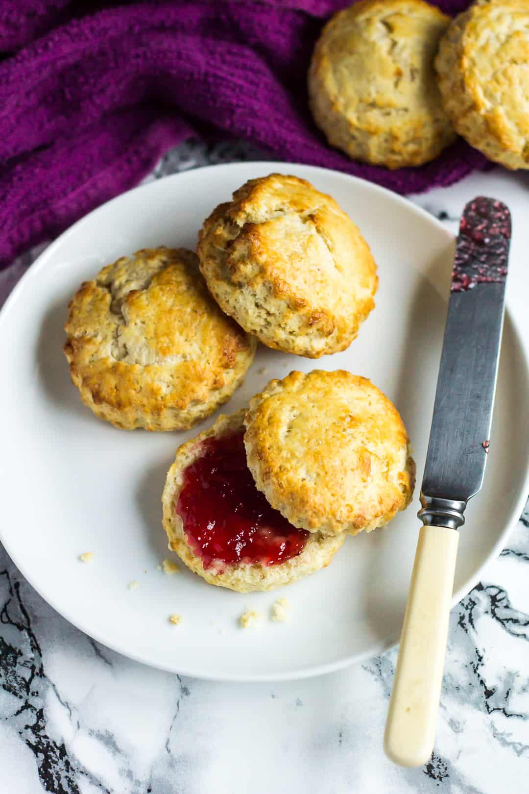 An overhead shot of Classic English Scones served on a small white plate. One scone is cut in half and filled with jam.