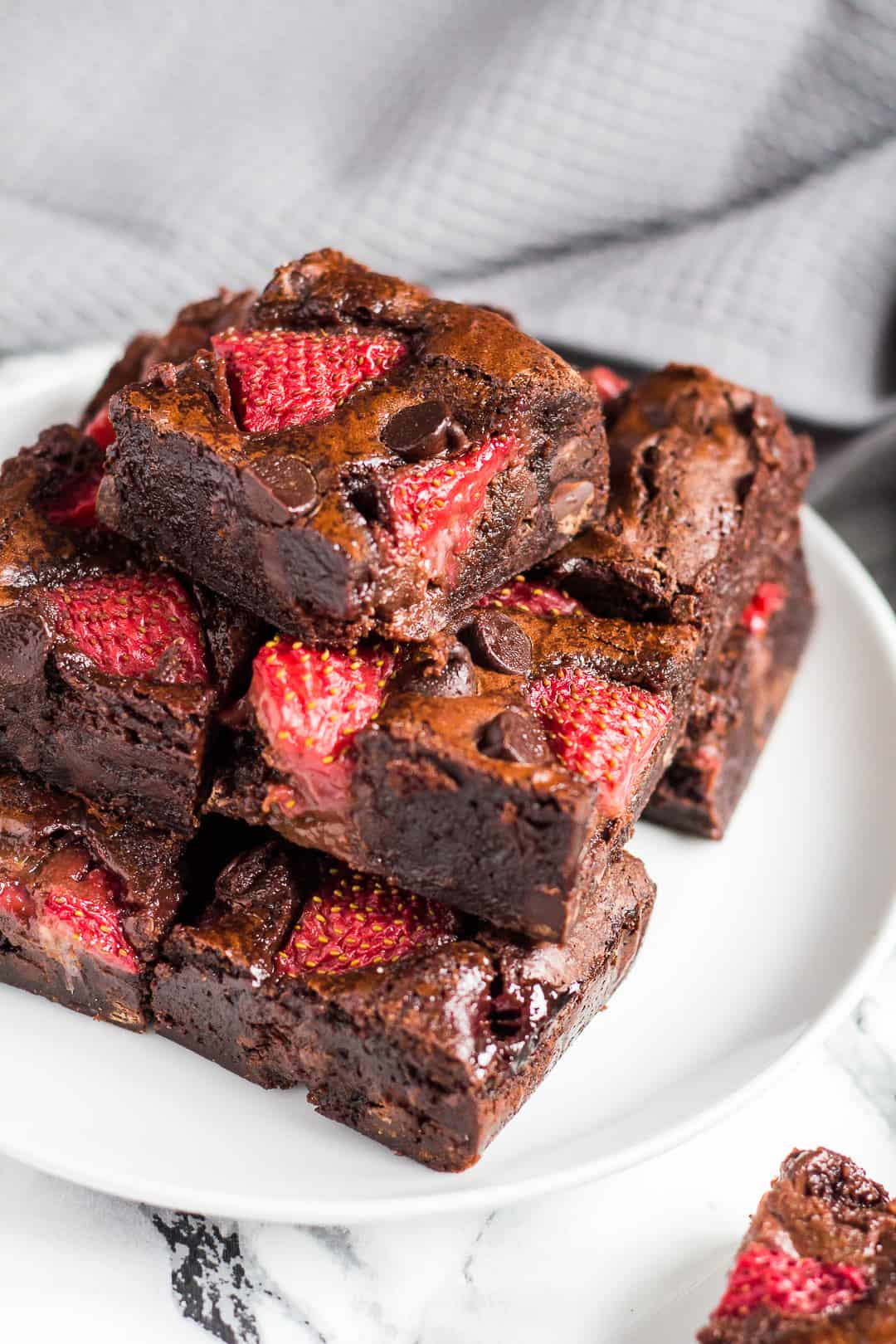 Strawberry mint brownies piled on top of each other on a small white plate.