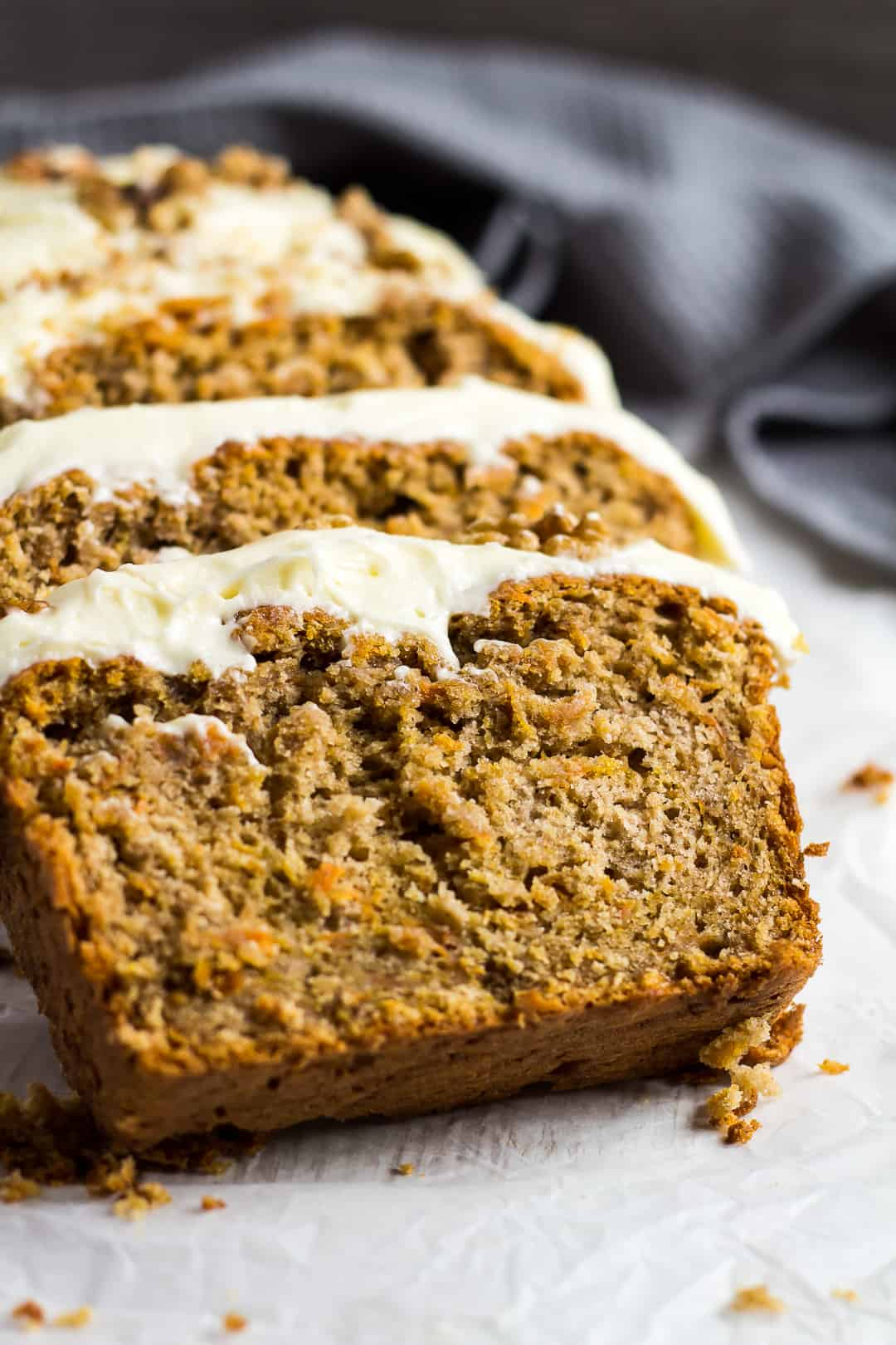 A row of Carrot Cake Loaf slices topped with cream cheese frosting overlapping each other.