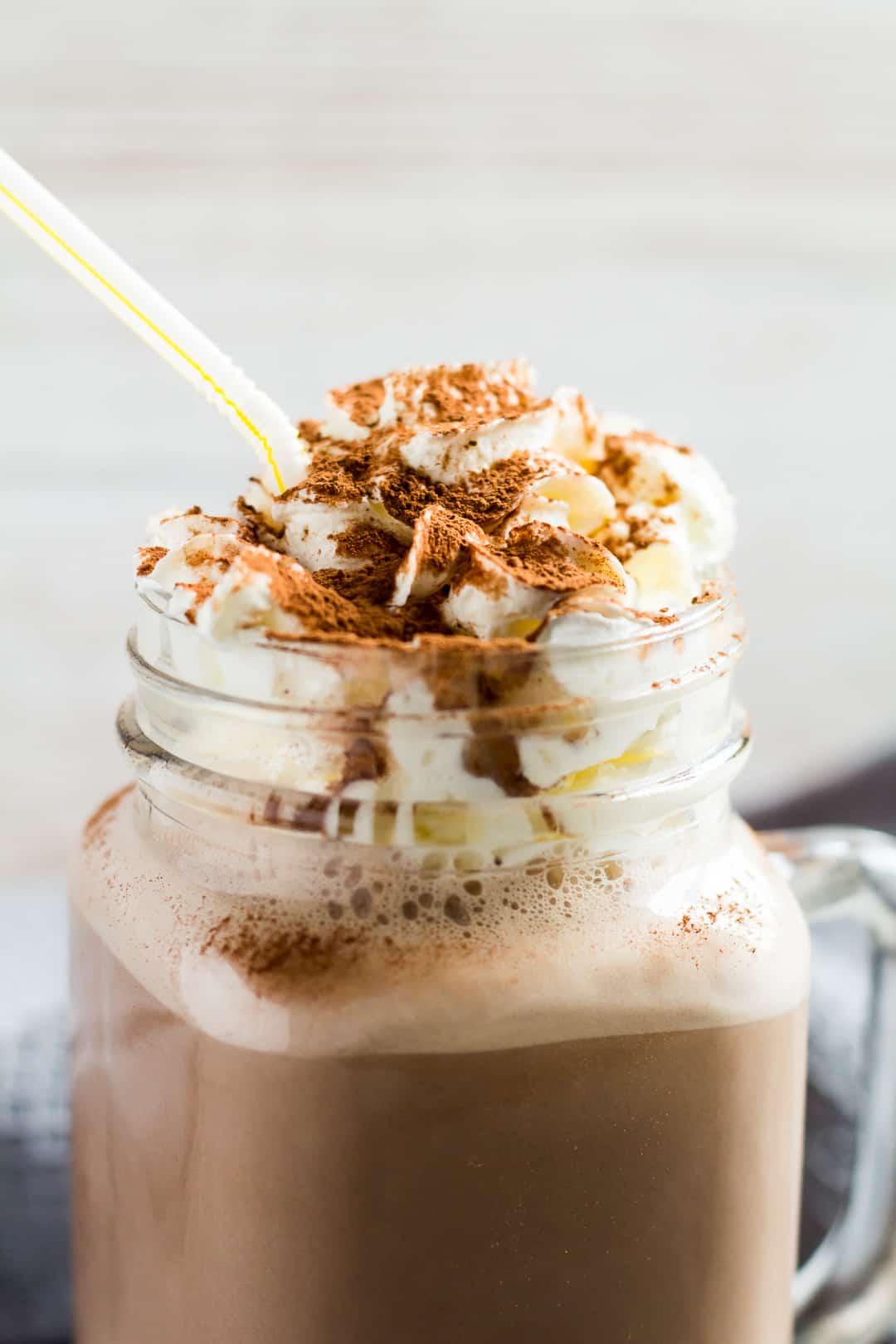 Chocolate Nesquik Milkshake in a glass mason jar topped with whipped cream and cocoa powder.