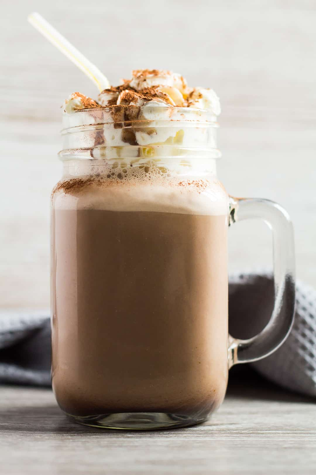 A sideview shot of Chocolate Nesquik Milkshake served in a glass mason jar with whipped cream and a straw.