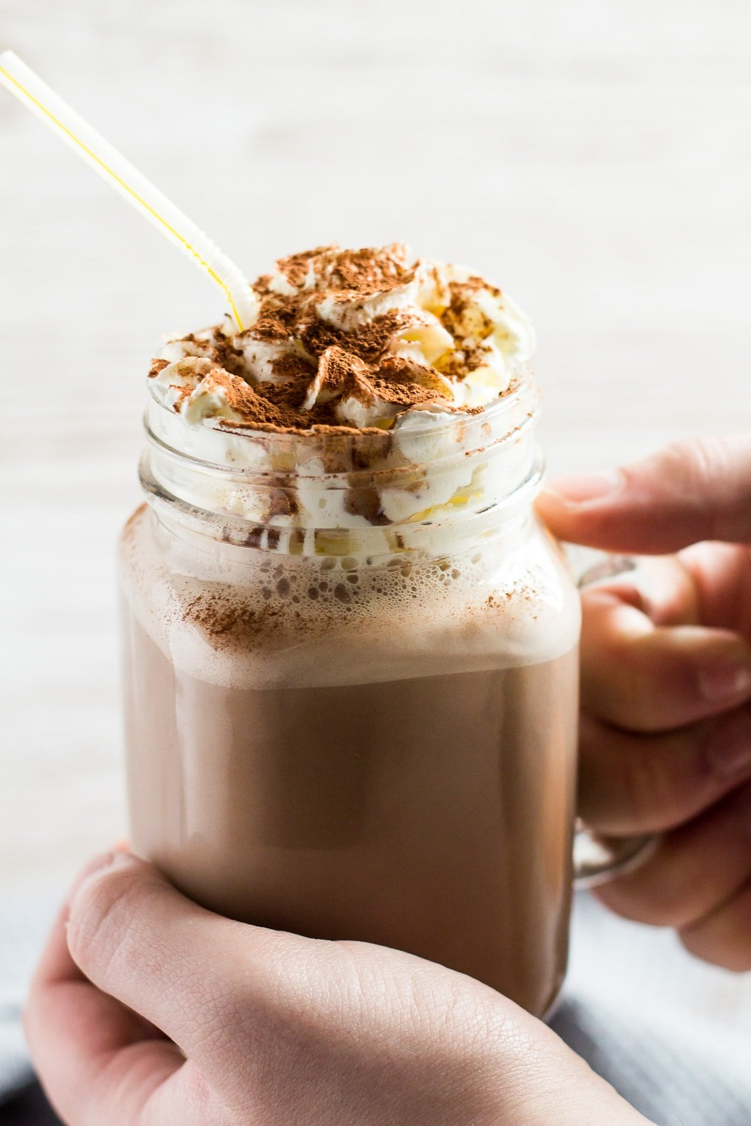 A glass mason jar filled with Chocolate Nesquik Milkshake topped with whipped cream being held by hand.