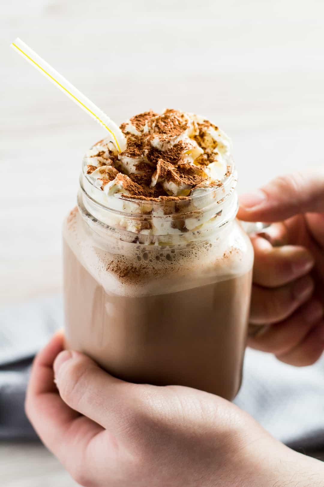 Chocolate Nesquik Milkshake topped with whipped cream in a glass mason jar being held by hand.