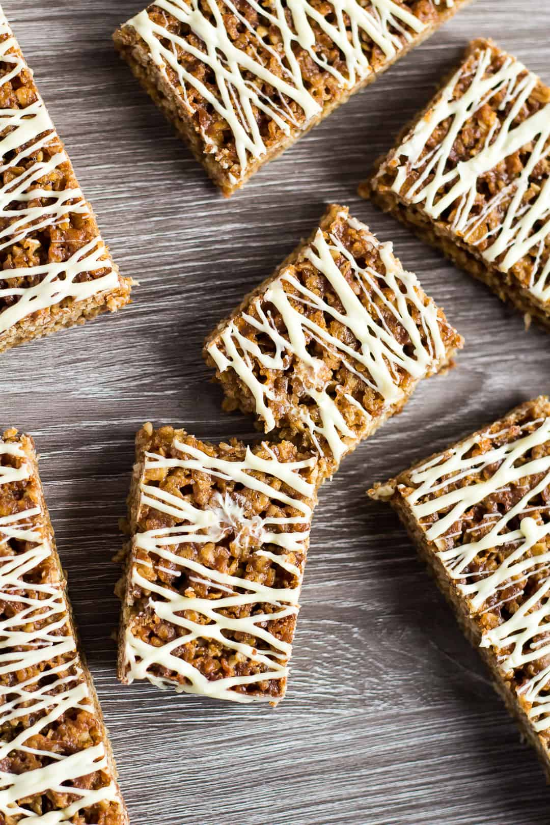 An overhead shot of Hot Cross Bun Spiced Flapjacks drizzled with white chocolate with one flapjack broke in half.