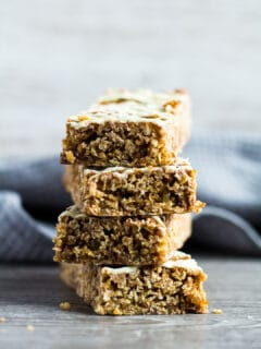 A sideview shot of Hot Cross Bun Spiced Flapjacks stacked on top of each other.