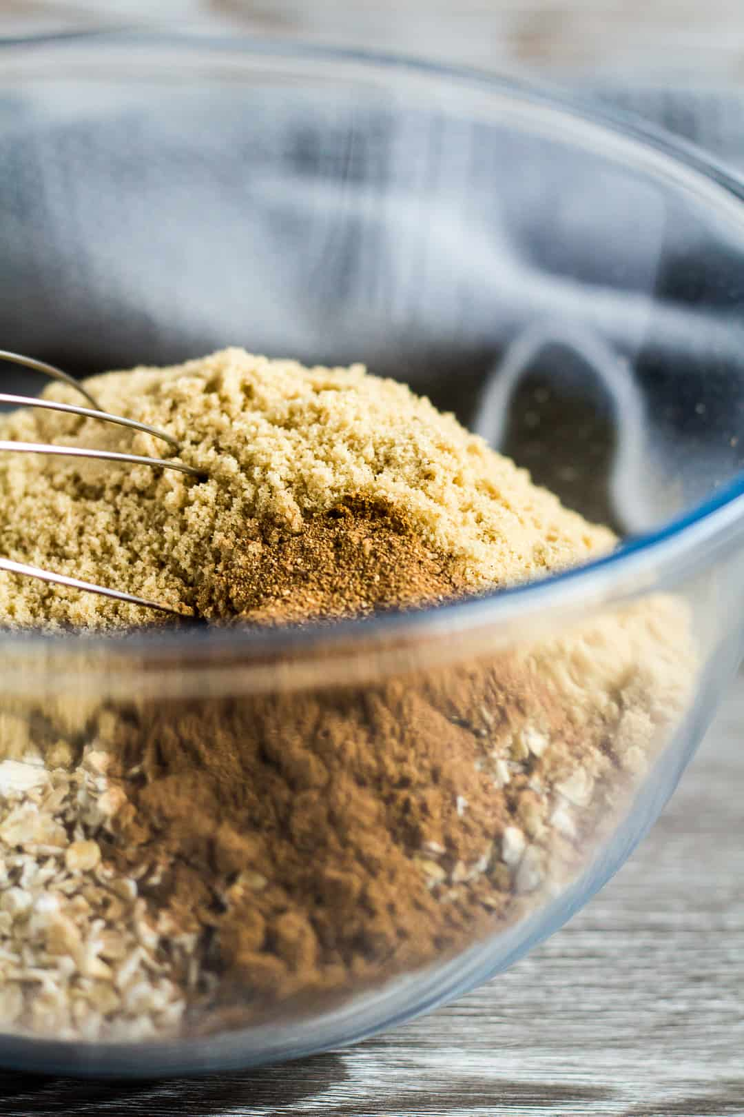 Oats, brown sugar, and spices in a glass mixing bowl for Hot Cross Bun Spiced Flapjacks.