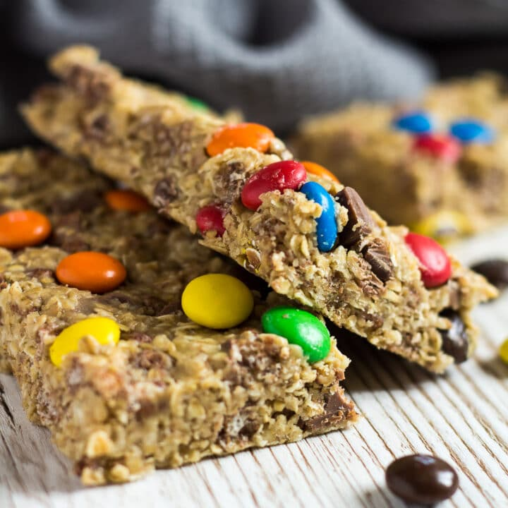A close-up shot of No-Bake Peanut Butter M&M Granola Bars overlapping each other.