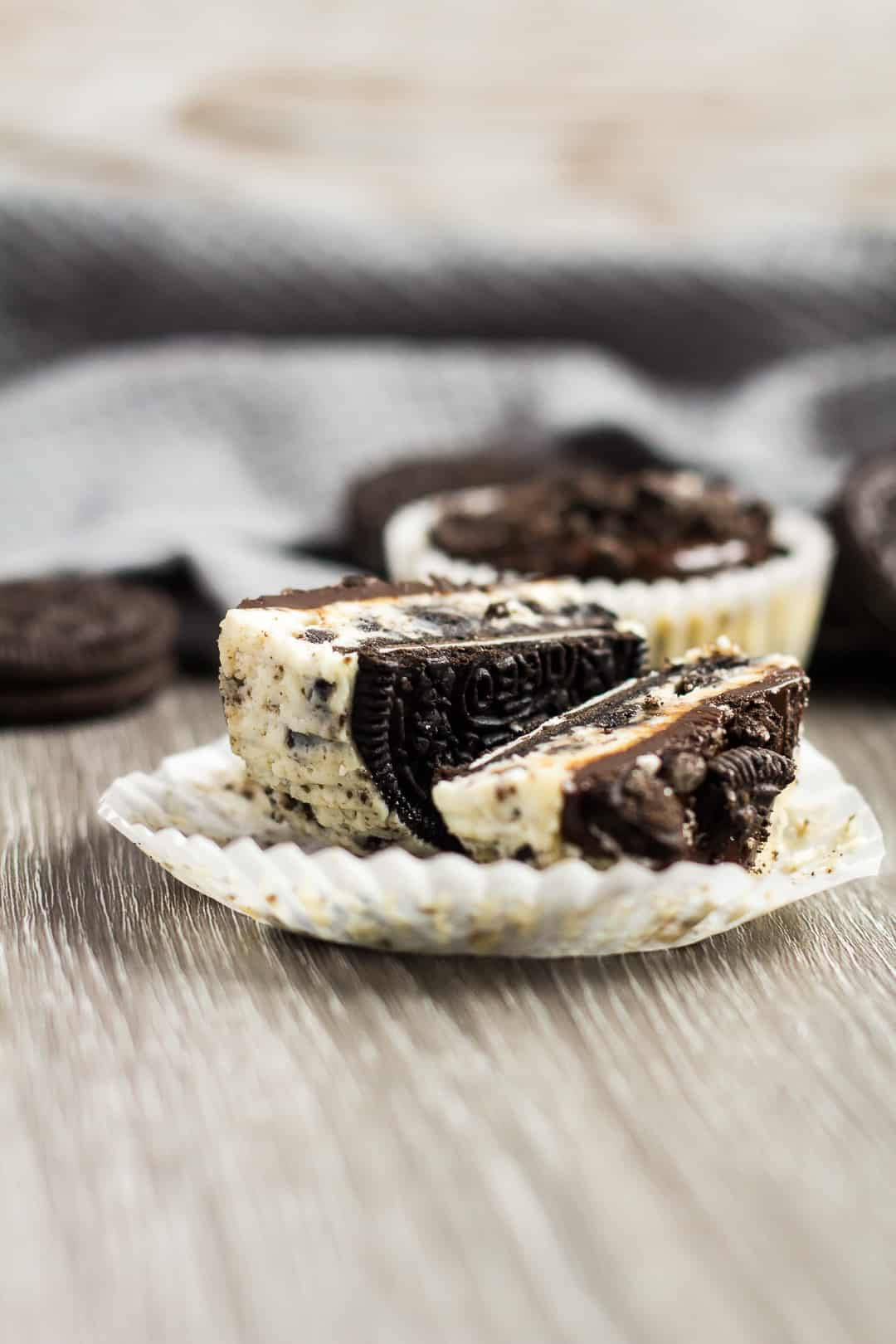 A sideview shot of a Mini Oreo Cheesecake cut in half and laid on its side to show whole Oreo crust.