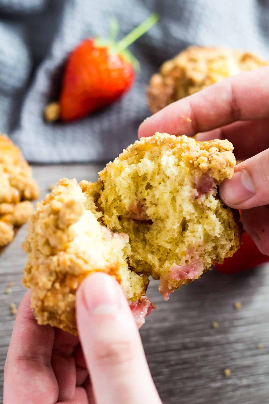 A Strawberry Crumb Muffin being pulled apart by hand.