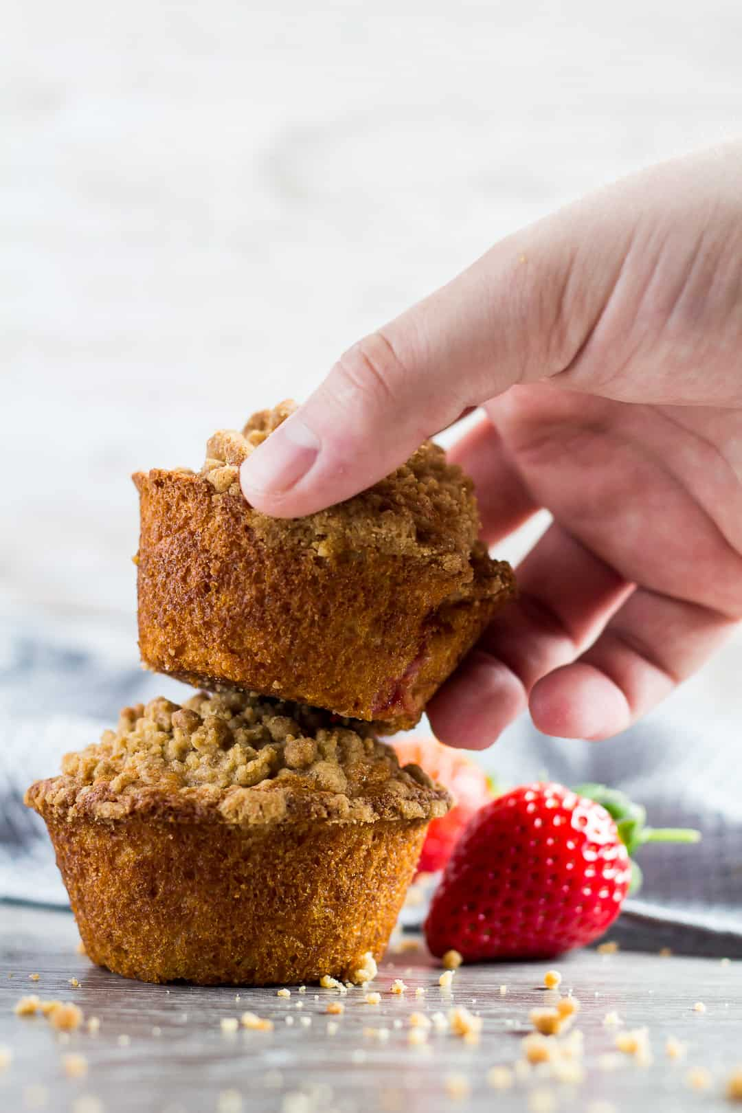 A Strawberry Crumb Muffin being picked up by hand.