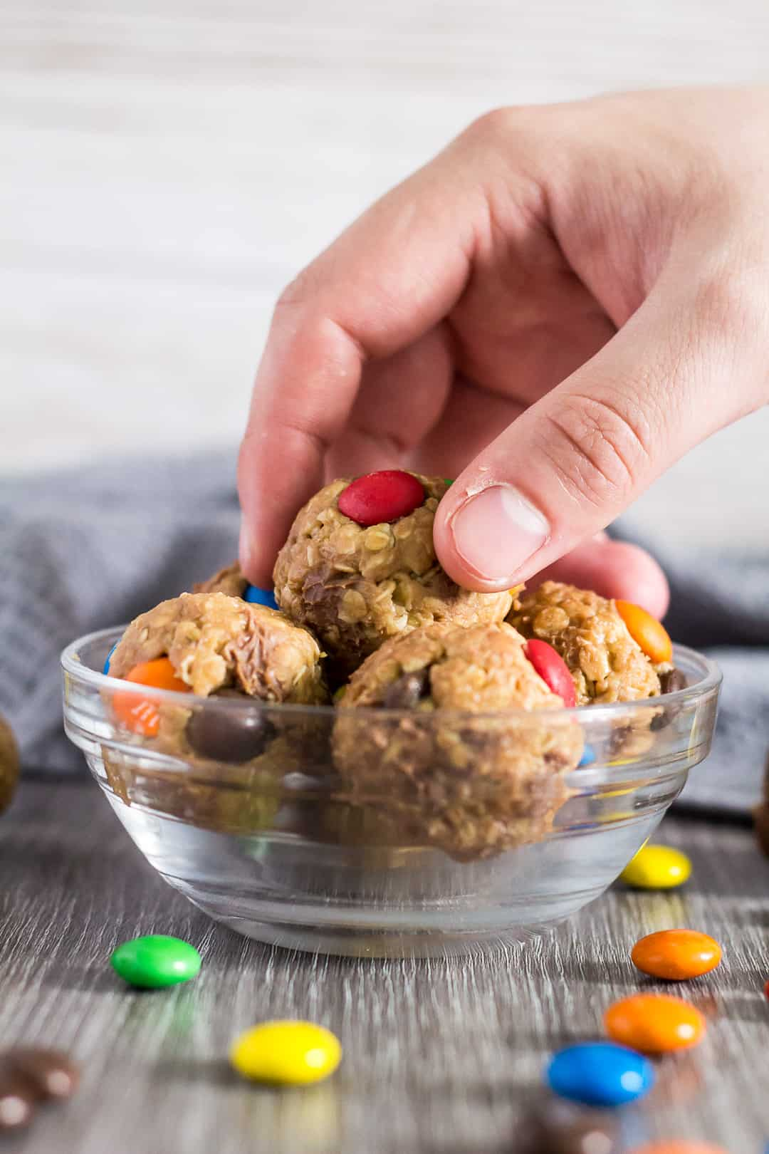 No-Bake Monster Cookie Bites in a small glass bowl. One being picked up by hand.