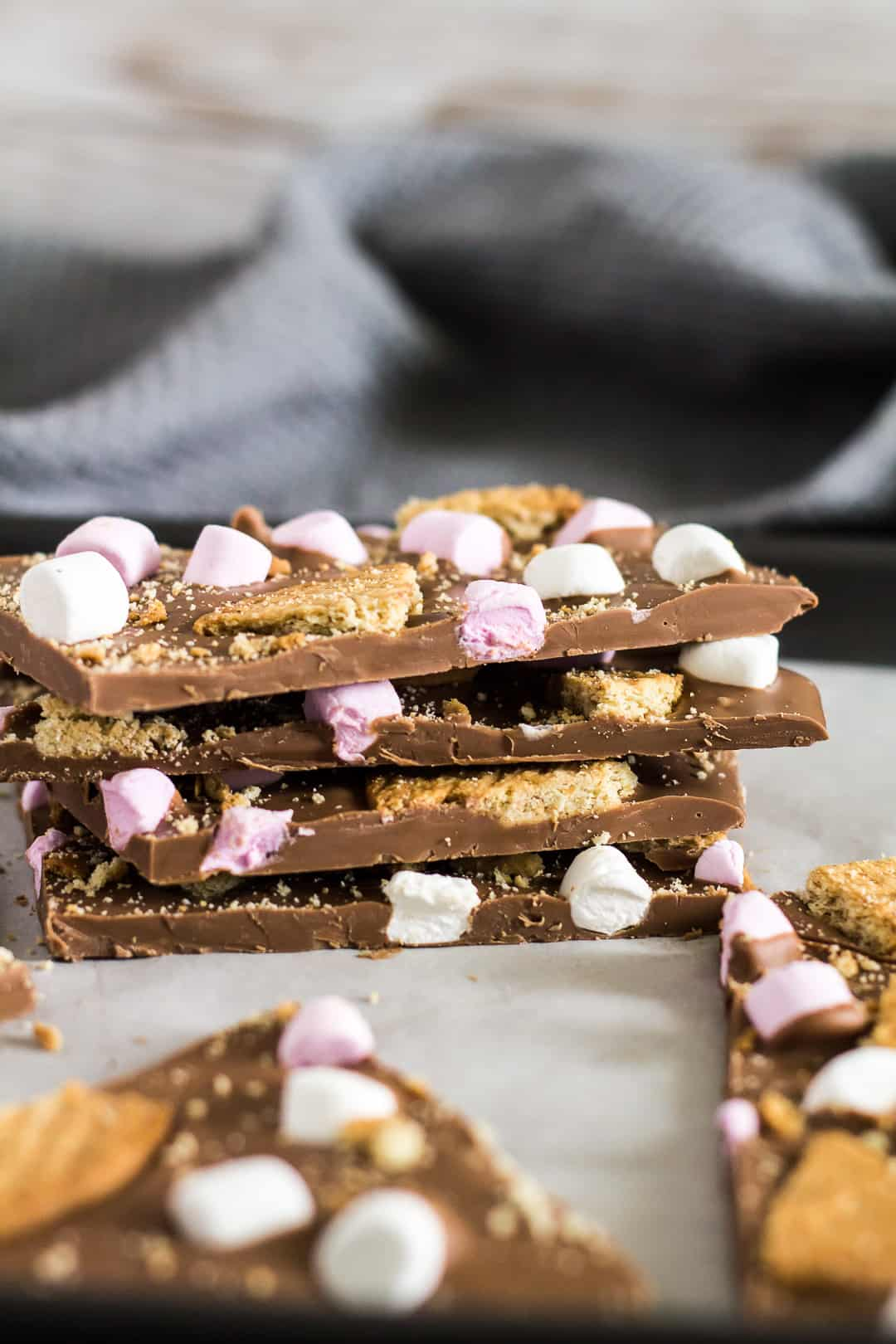 A stack of four pieces of S'mores Chocolate Bark on a baking tray.