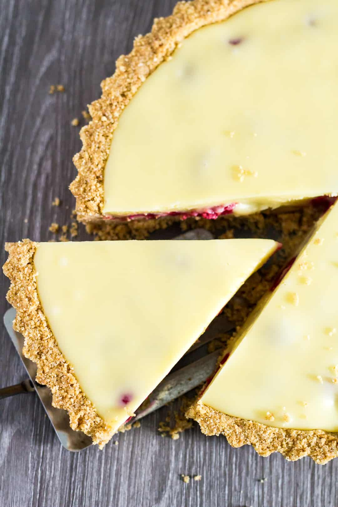 Overhead shot of White Chocolate Raspberry Tart with slice being removed.