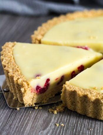 White Chocolate Raspberry Tart with slice being taken.