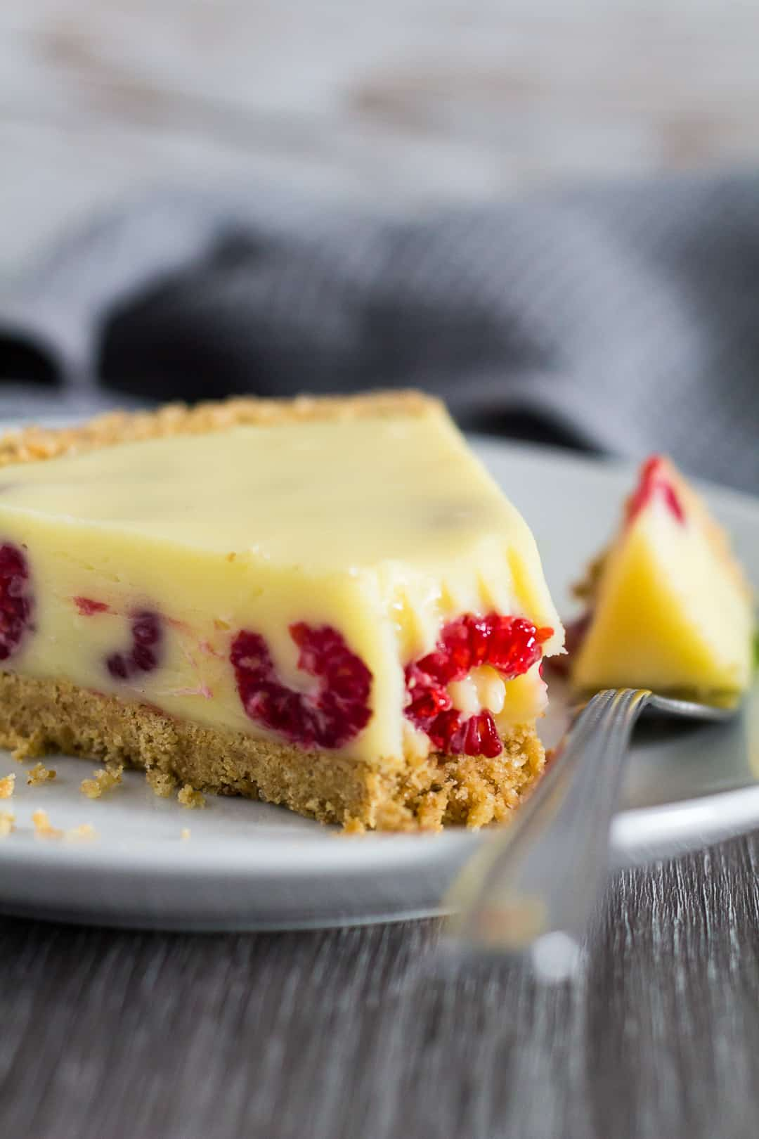 A slice of White Chocolate Raspberry Tart served on white plate with fork.