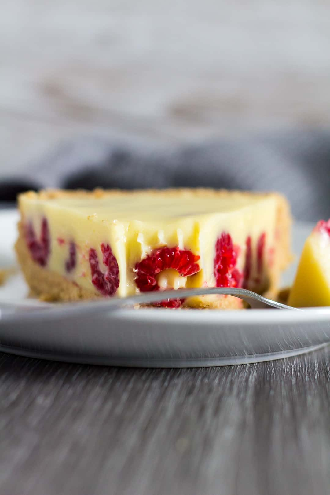 Slice of White Chocolate Raspberry Tart served on white plate with a fork.