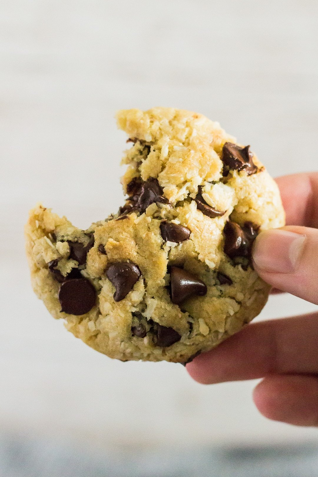 A bitten Coconut Chocolate Chip Cookie being held up by hand.