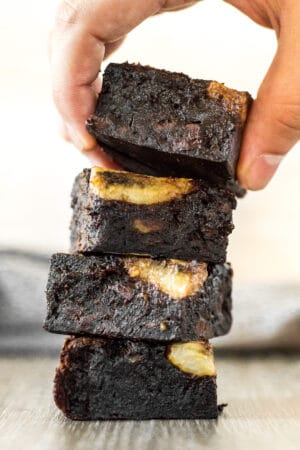 A stack of Fudgy Banana Brownies with the top brownie being picked up by hand.