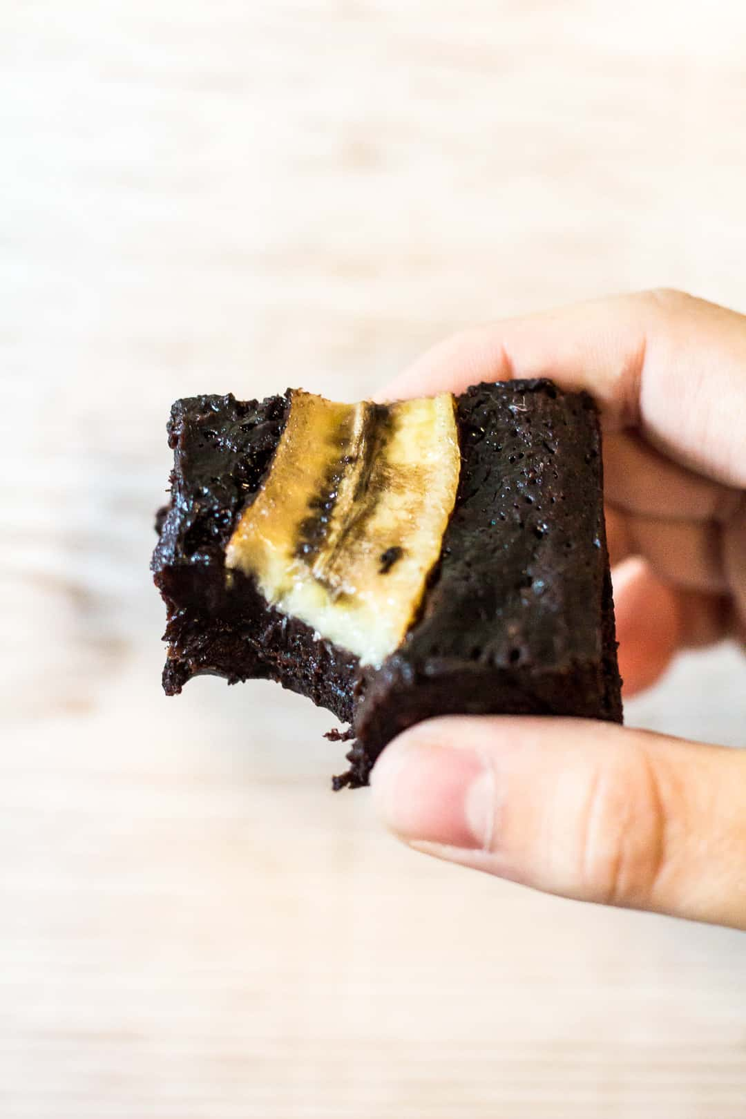 A bitten Fudgy Banana Brownie being held up by hand.